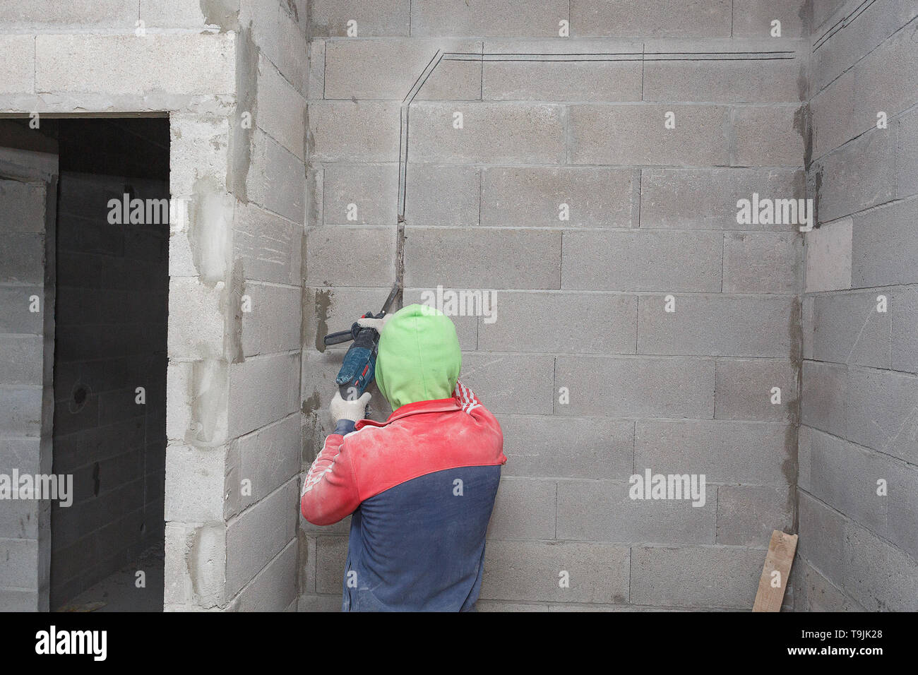 A laborer prepares a wall for laying electrical wiring, while building a residential  house Stock Photo - AlamyAlamy