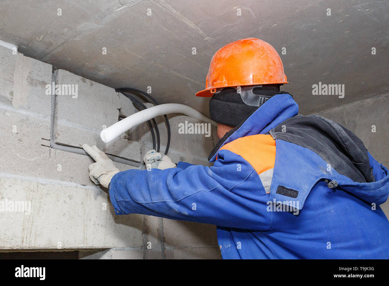 The worker in the helmet is laying electrical wiring during the roughing phase. - Stock Image