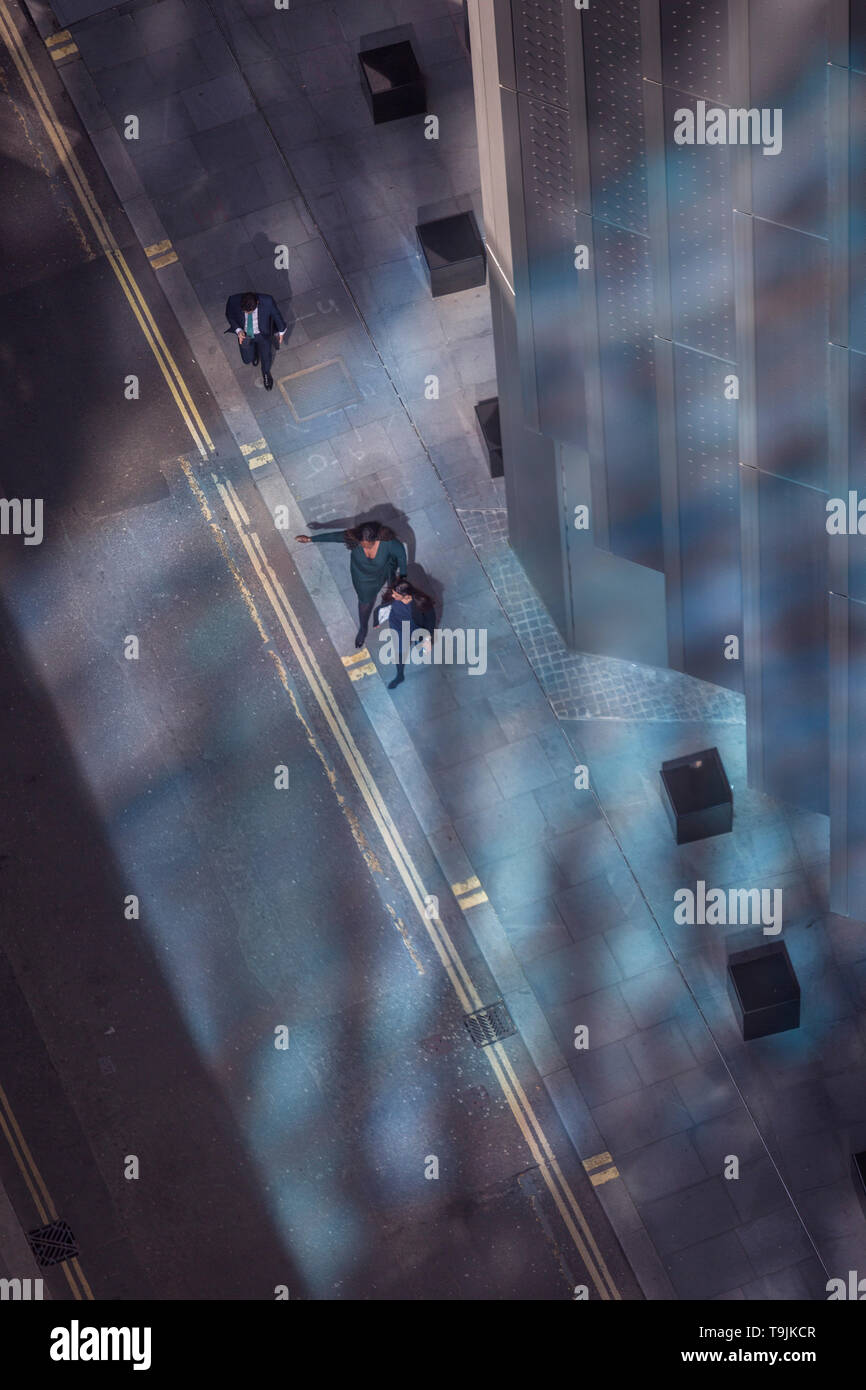 Looking down from an aerial view towards small business figures walking through blue reflected light in the City of London, the capital's ancient financial district, on 13th May, in London, England. - Stock Image