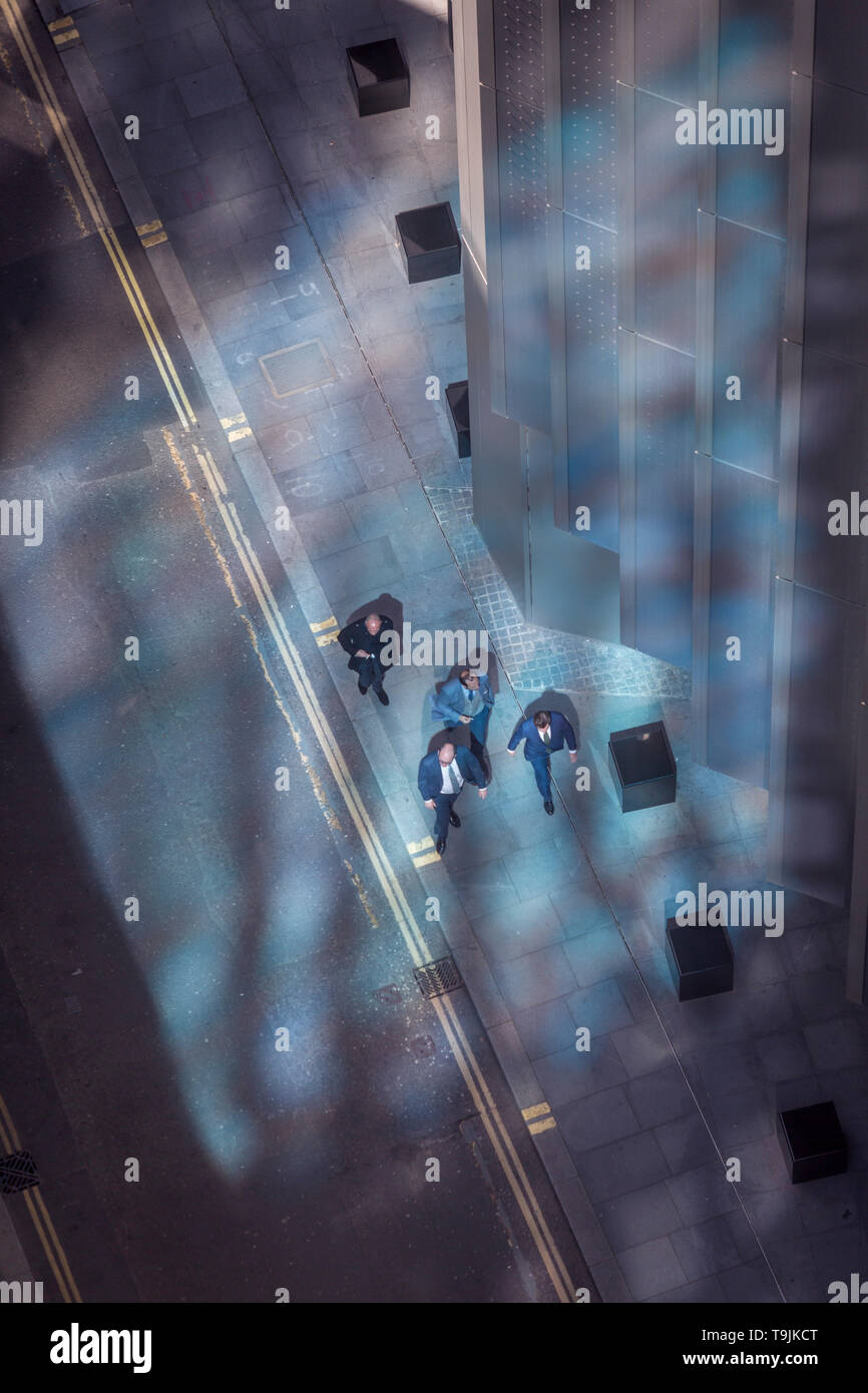 Looking down from an aerial view towards small business figures walking through blue reflected light in the City of London, the capital's ancient financial district, on 13th May, in London, England. Stock Photo