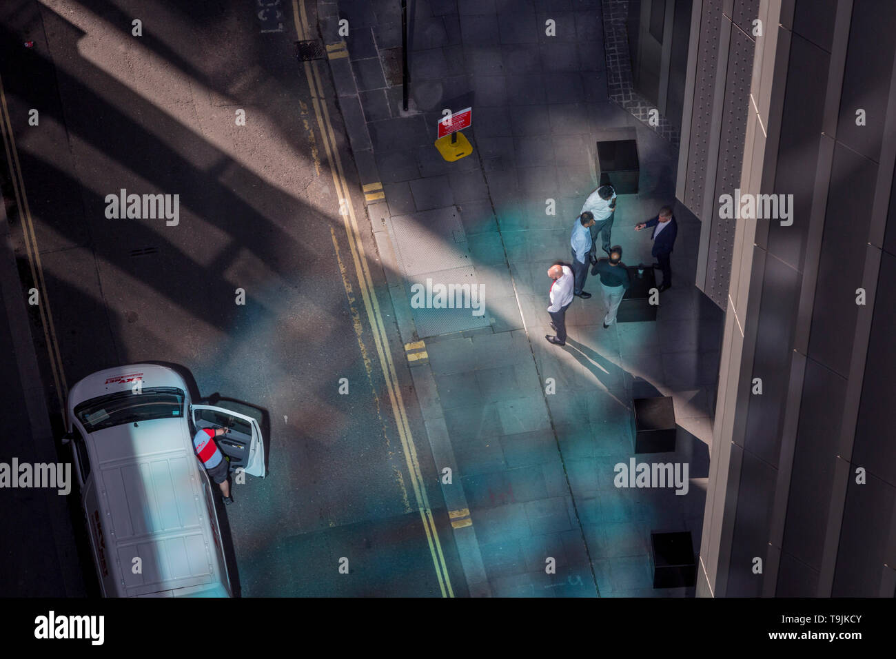 Looking down from an aerial view towards a courier driver and small business figures walking through blue reflected light in the City of London, the capital's ancient financial district, on 13th May, in London, England. - Stock Image