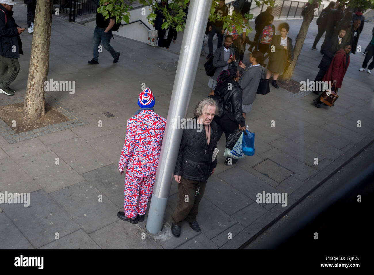 A man wearing a patriotic Union Jack suit waits for the next bus along with other commuters at Elephant & Castle in Southwark, south London, on 10th May 2019, in London, England. - Stock Image