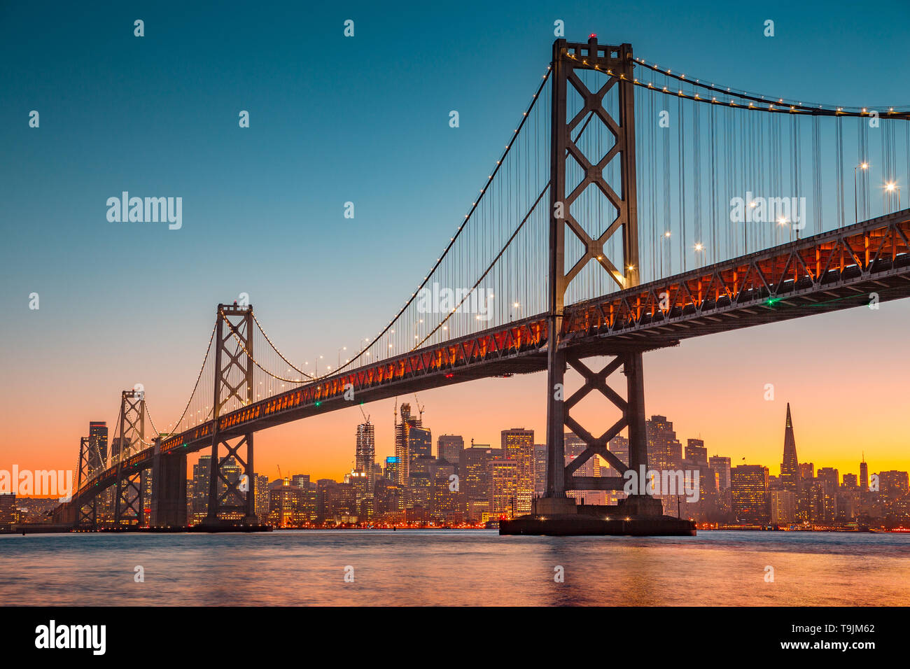 Classic panoramic view of San Francisco skyline with famous Oakland Bay Bridge illuminated in beautiful golden evening light at sunset in summer, San  - Stock Image