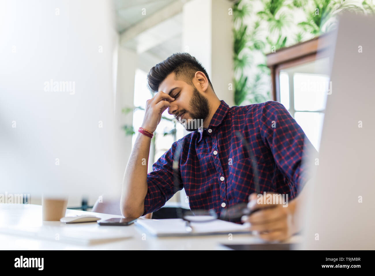 Photo of an Indian male frustrated with work sitting in front of a laptop. - Stock Image
