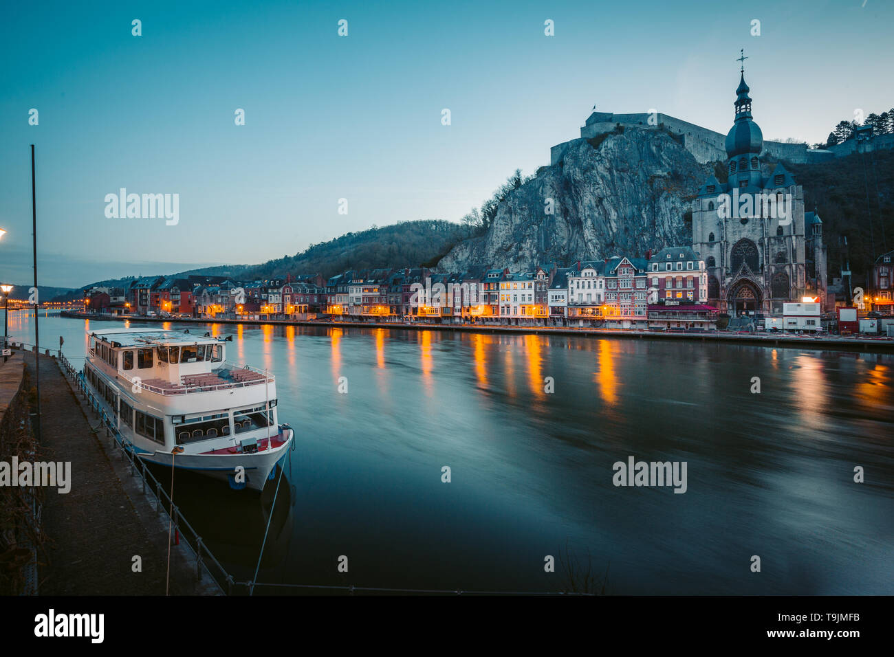 Classic view of the historic town of Dinant with scenic River Meuse in beautiful evening twilight light during blue hour at dusk, province of Namur, W - Stock Image