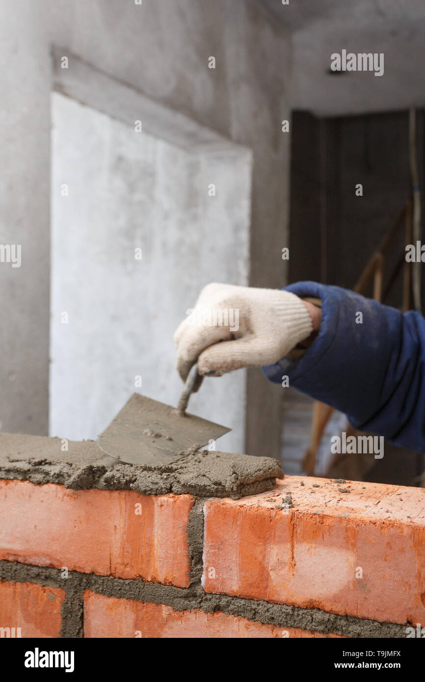Hand in the process of laying a wall of red brick. - Stock Image