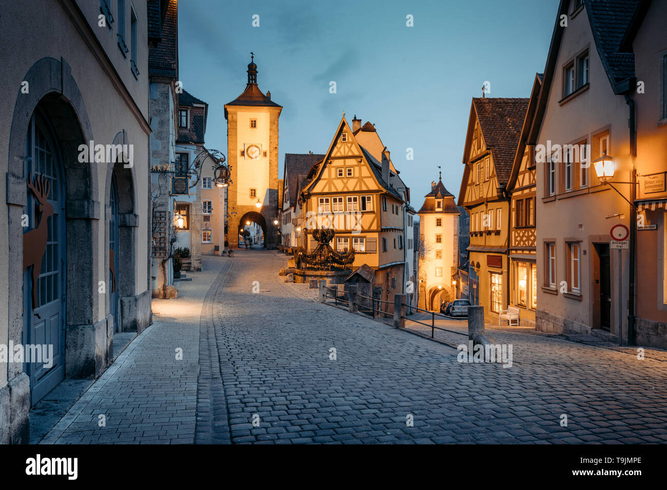 Classic view of the medieval town of Rothenburg ob der Tauber illuminated in beautiful evening twilight during blue hour at dusk, Bavaria, Germany - Stock Image