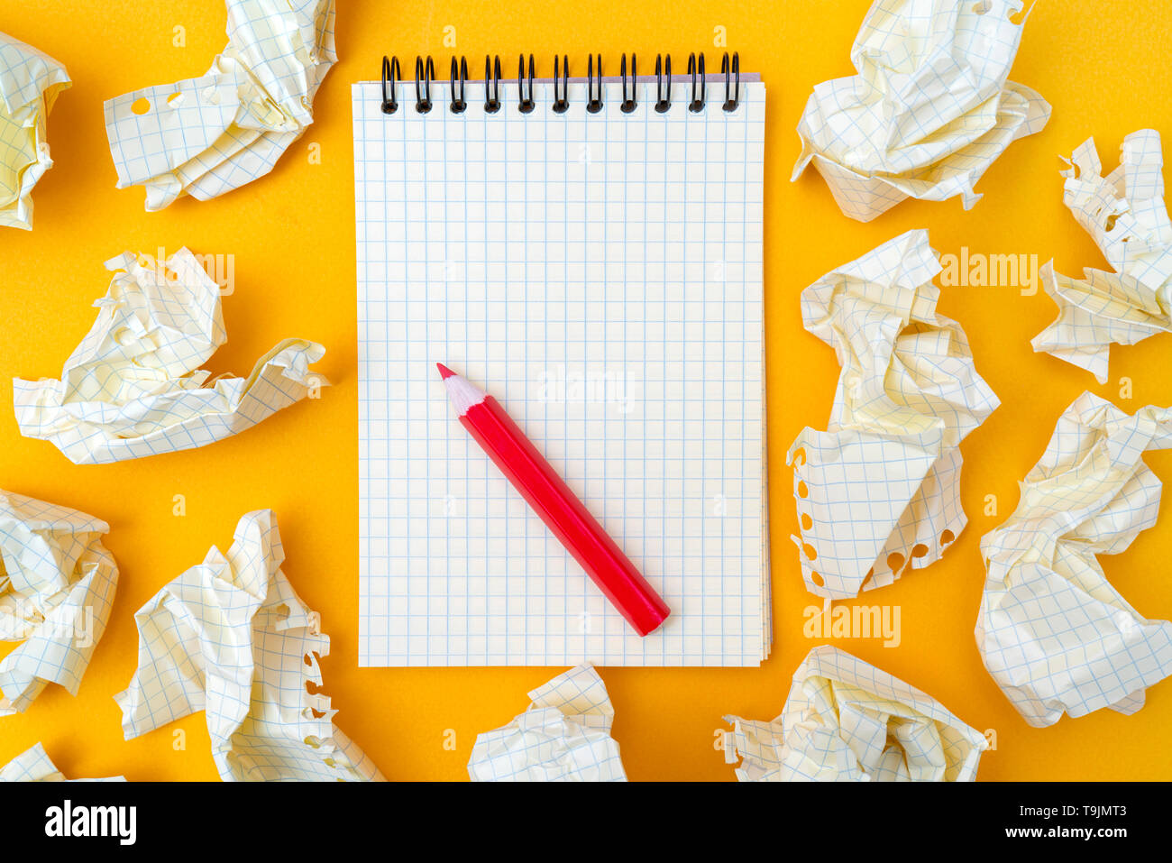 Red pencil and notebook on a yellow background. Crumpled sheets of paper. - Stock Image