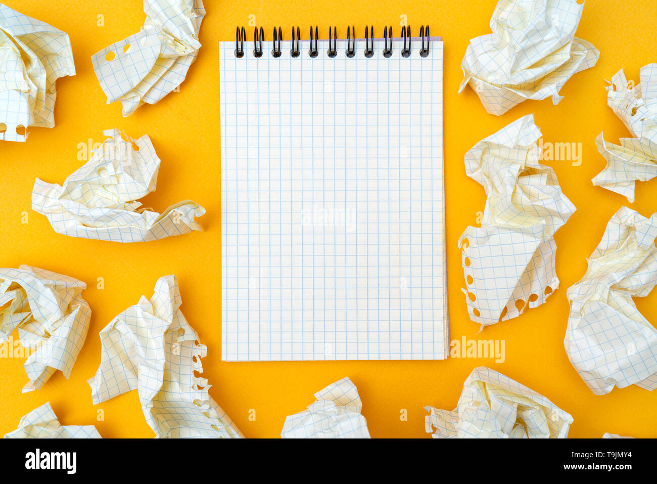 Notepad and crumpled sheets of paper on a yellow background. - Stock Image