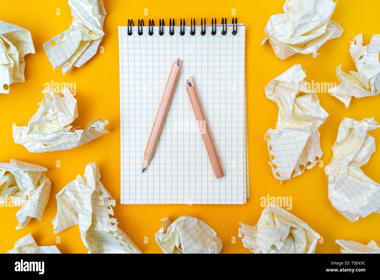 Pencil and notebook on a yellow background. Crumpled sheets of paper. - Stock Image