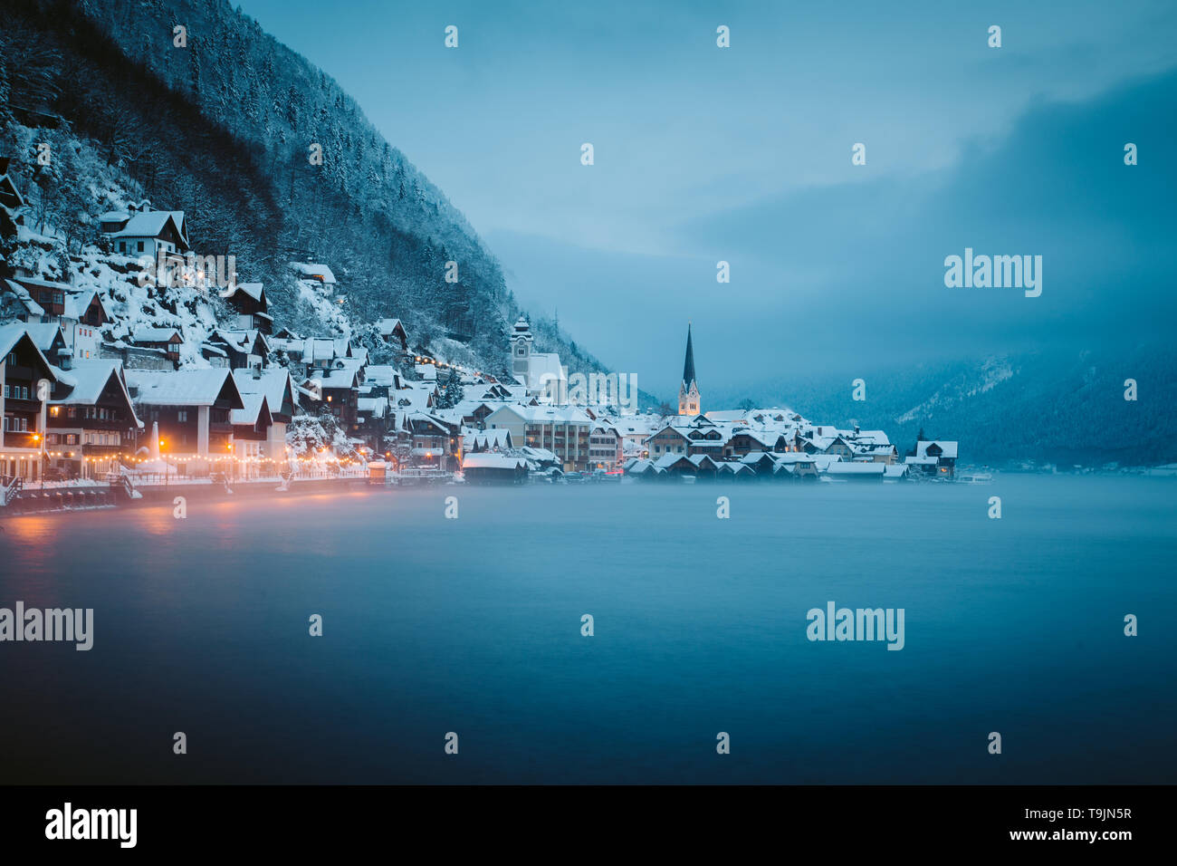 Panorama view of famous Hallstatt lakeside town in the Alps in mystic twilight during blue hour at dawn on a beautiful cold foggy day in winter, Salzk - Stock Image