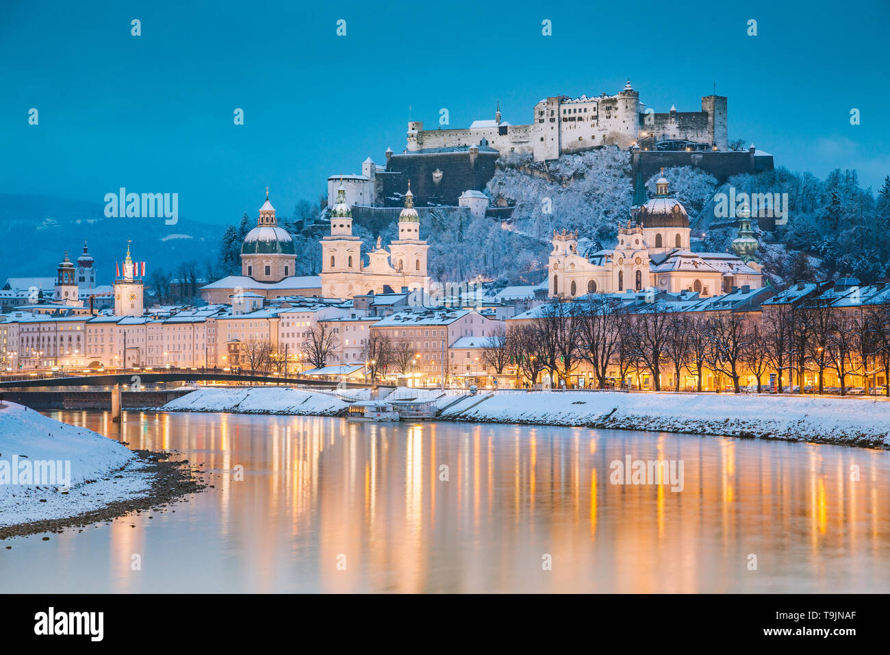 Classic view of the historic city of Salzburg with famous Festung Hohensalzburg and Salzach river illuminated in beautiful twilight during scenic Chri - Stock Image