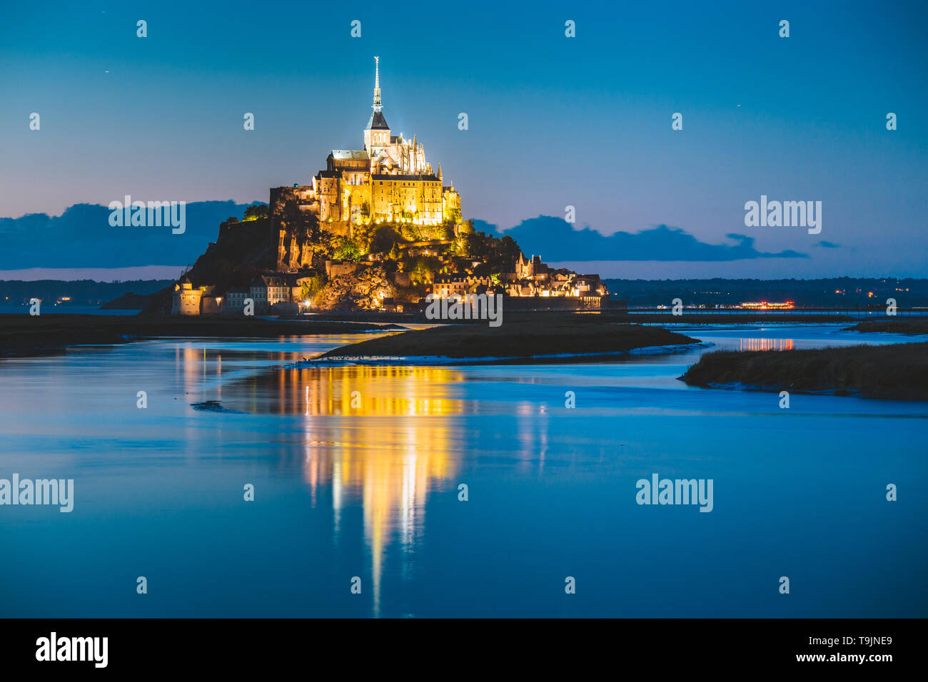 Classic view of famous Le Mont Saint-Michel tidal island in beautiful twilight during blue hour at dusk, Normandy, northern France - Stock Image