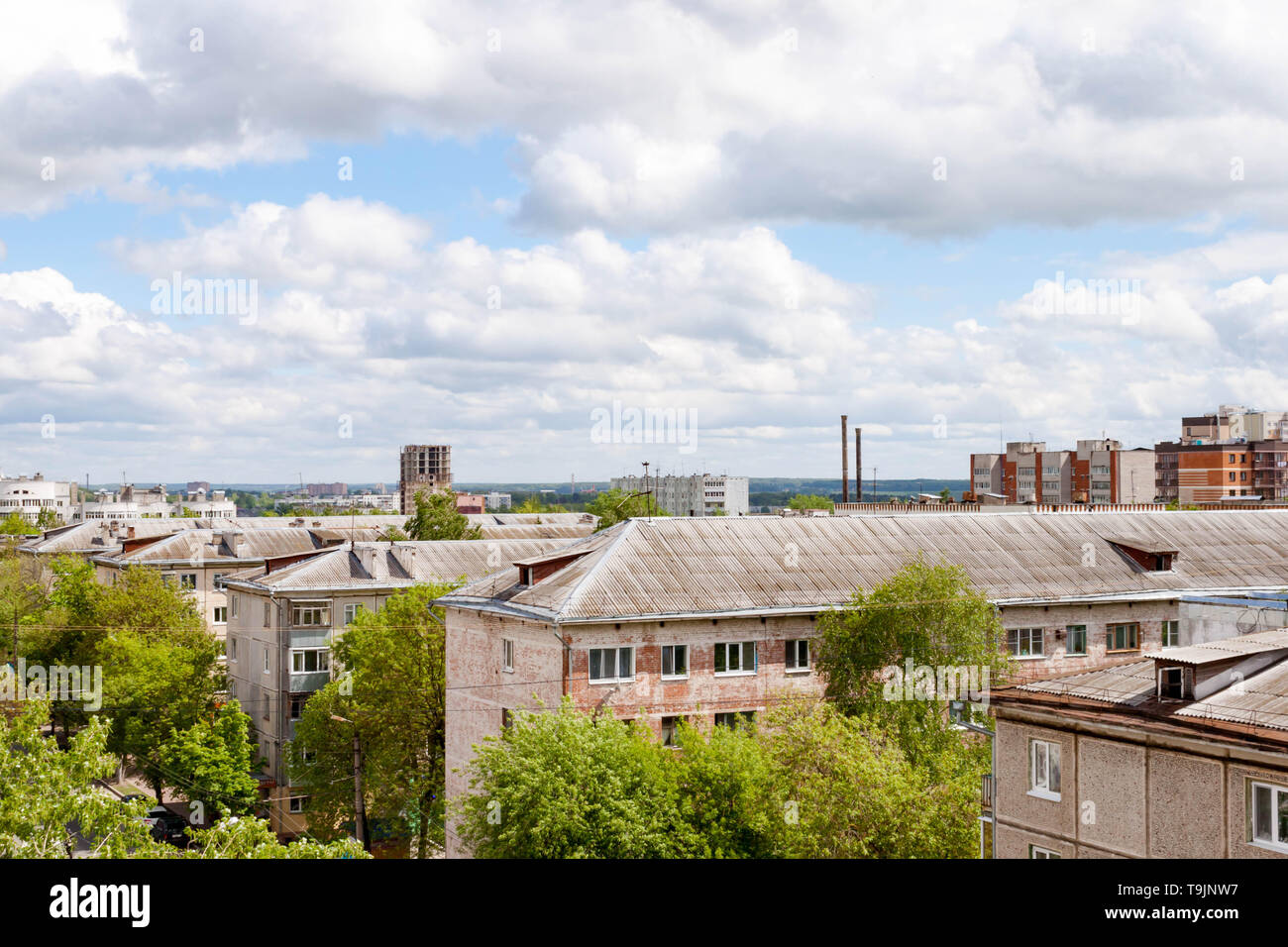 Kaluga, Russia - May 11, 2019: View of roofs of old brick 5 storey houses from the Sky restaurant. Industrial landscape on cloudy sky background. - Stock Image