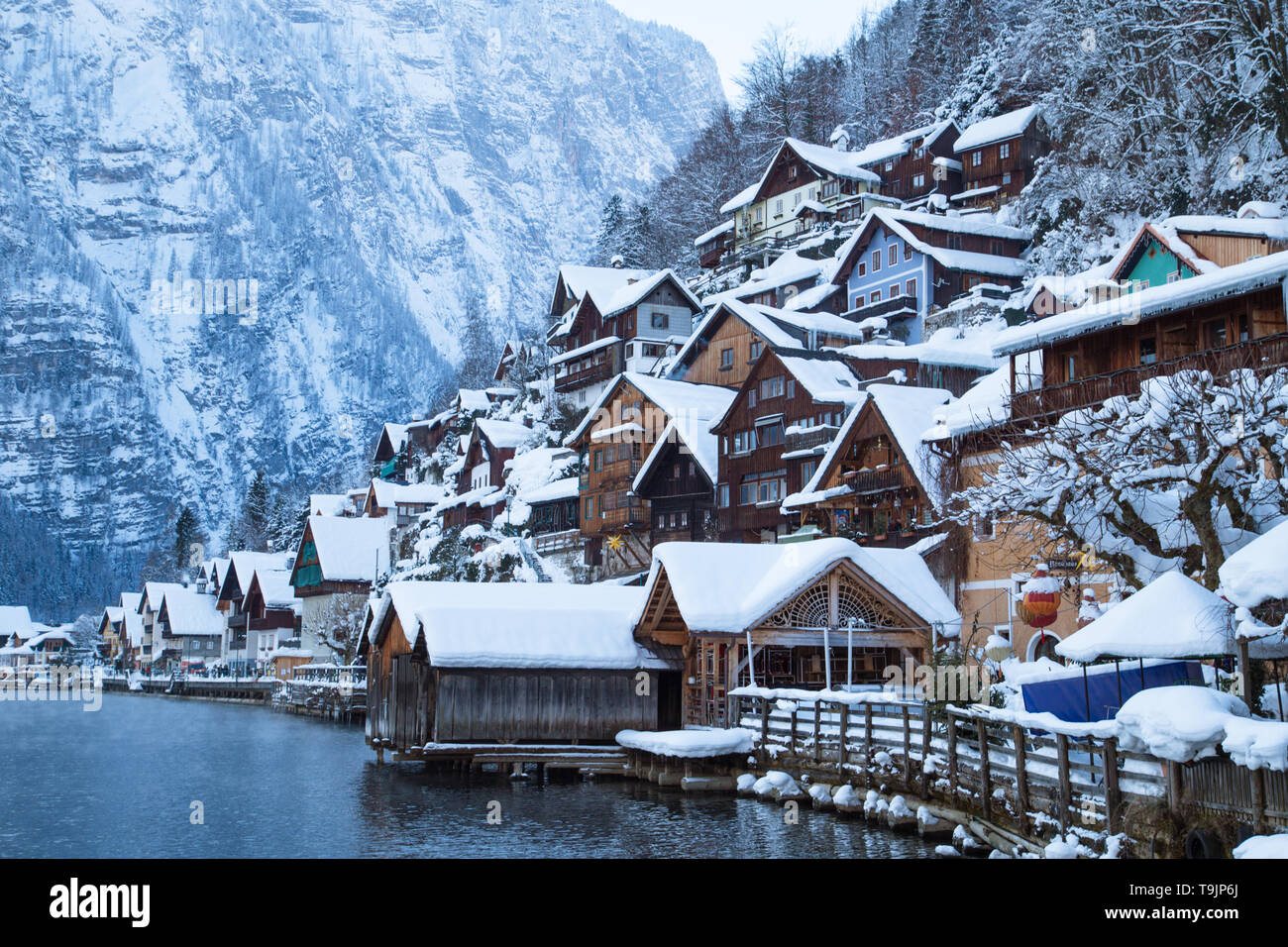 Classic postcard view of traditional wooden houses in famous Hallstatt lakeside town in the Alps in mystic twilight during blue hour at dawn on a beau - Stock Image