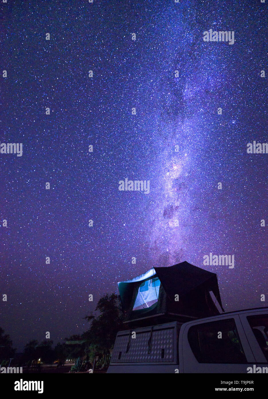 Milky way over a tent on the roof of a pickup car in the Namib desert of Namibia - Stock Image