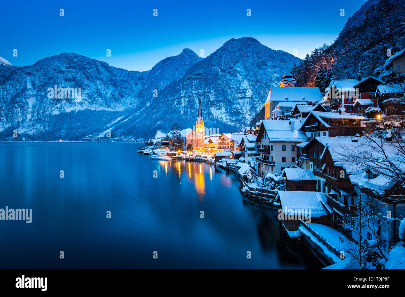 Classic postcard view of famous Hallstatt lakeside town in the Alps with beautiful Hallstattersee in mystical post sunset twilight during blue hour at - Stock Image