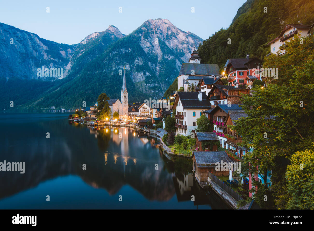 Classic postcard view of famous Hallstatt mountain village with Hallstattersee in the Austrian Alps in mystic twilight during blue hour at dawn in sum - Stock Image