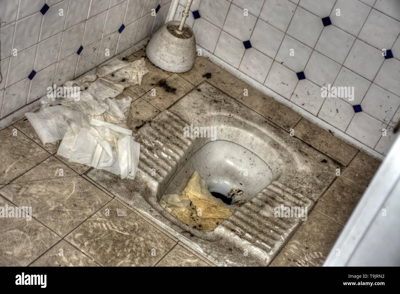 WC, Klo, Klosett, Toilette, Stand-WC, Standklo, verdreckt, verschmutzt, Trittfläche, Abort, Klobesen, Fliesen, WC-Papier, Klopapier, unappetitlich, gr - Stock Image