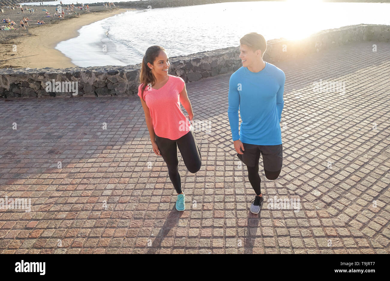 Sporty couple stretching legs next to the beach - Young lovers traning together on summer day outdoor - Sport, relationship, healthy lifestyle concept - Stock Image