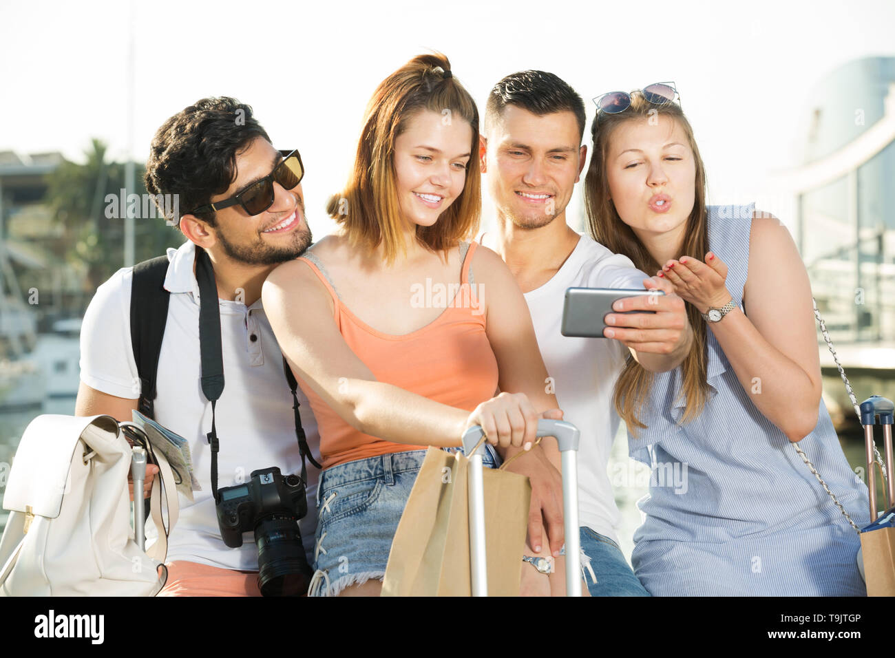 Group of friends taking selfie on camera in smartphone on waterfront in town on summer day - Stock Image
