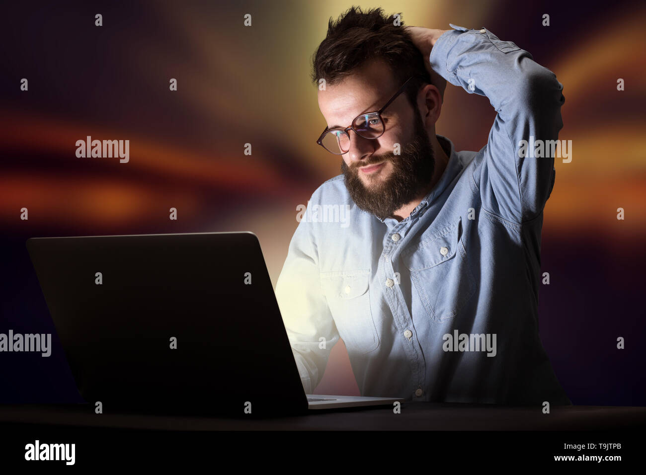 Young handsome businessman working late at night in the office with warm lights in the background - Stock Image
