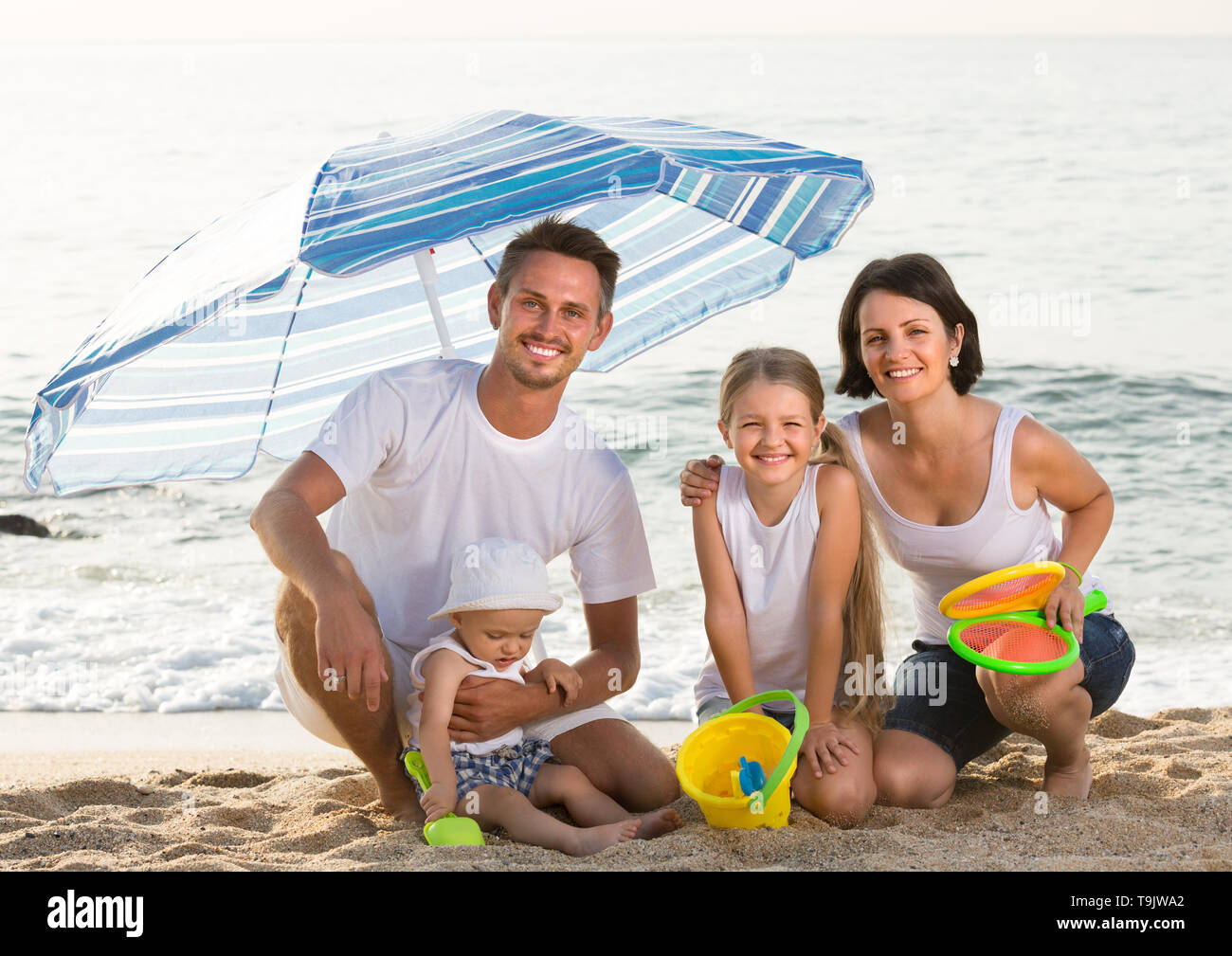 smiling parents with two kids sitting under sun umbrella with sand toys on beach - Stock Image