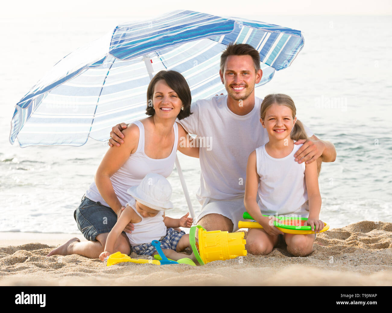 man and woman with two children sitting with plastic bucket and scoops under sun umbrella outdoors - Stock Image
