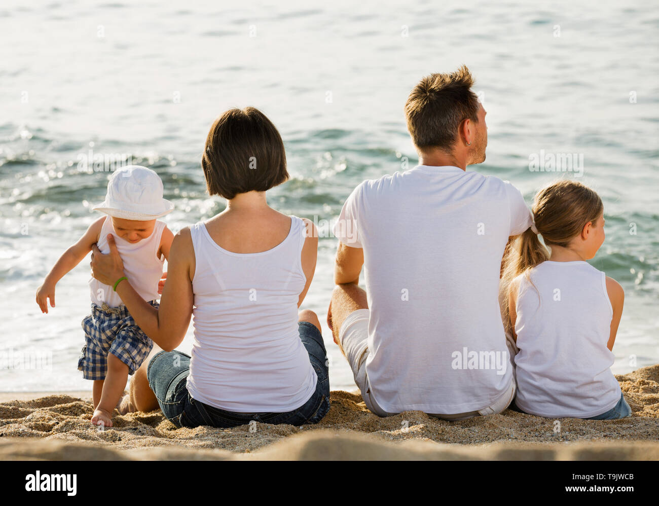 Happy glad  man and woman with two kids sitting with back to camera on sandy beach - Stock Image