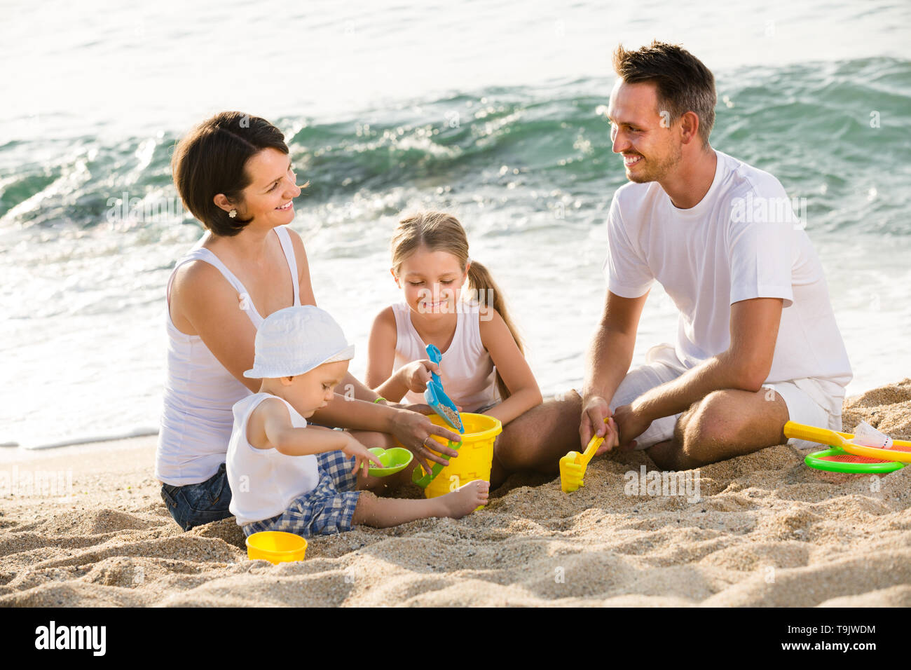 Smiling man and woman with two children playing with plastic bucket and scoops at beach - Stock Image