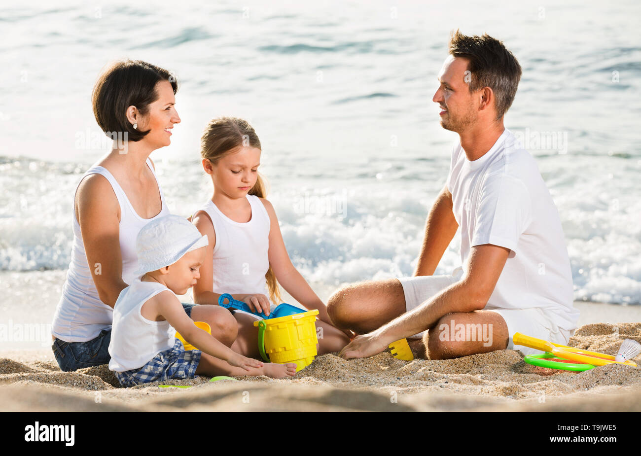 Cheerful positive  parents with two kids playing with sand toys on beach - Stock Image
