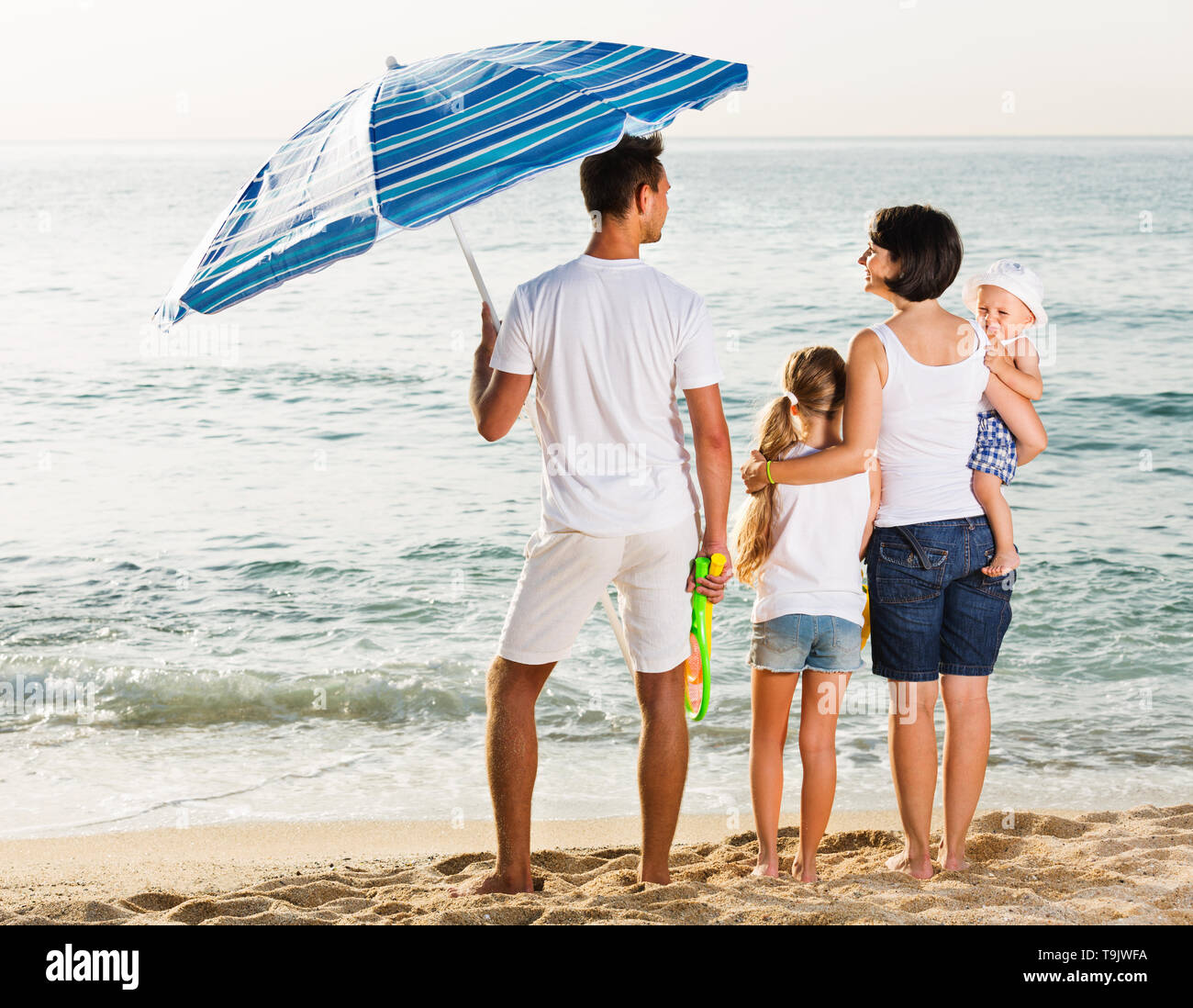 Smiling happy glad man and woman with two children standing with back to camera on sandy beach - Stock Image
