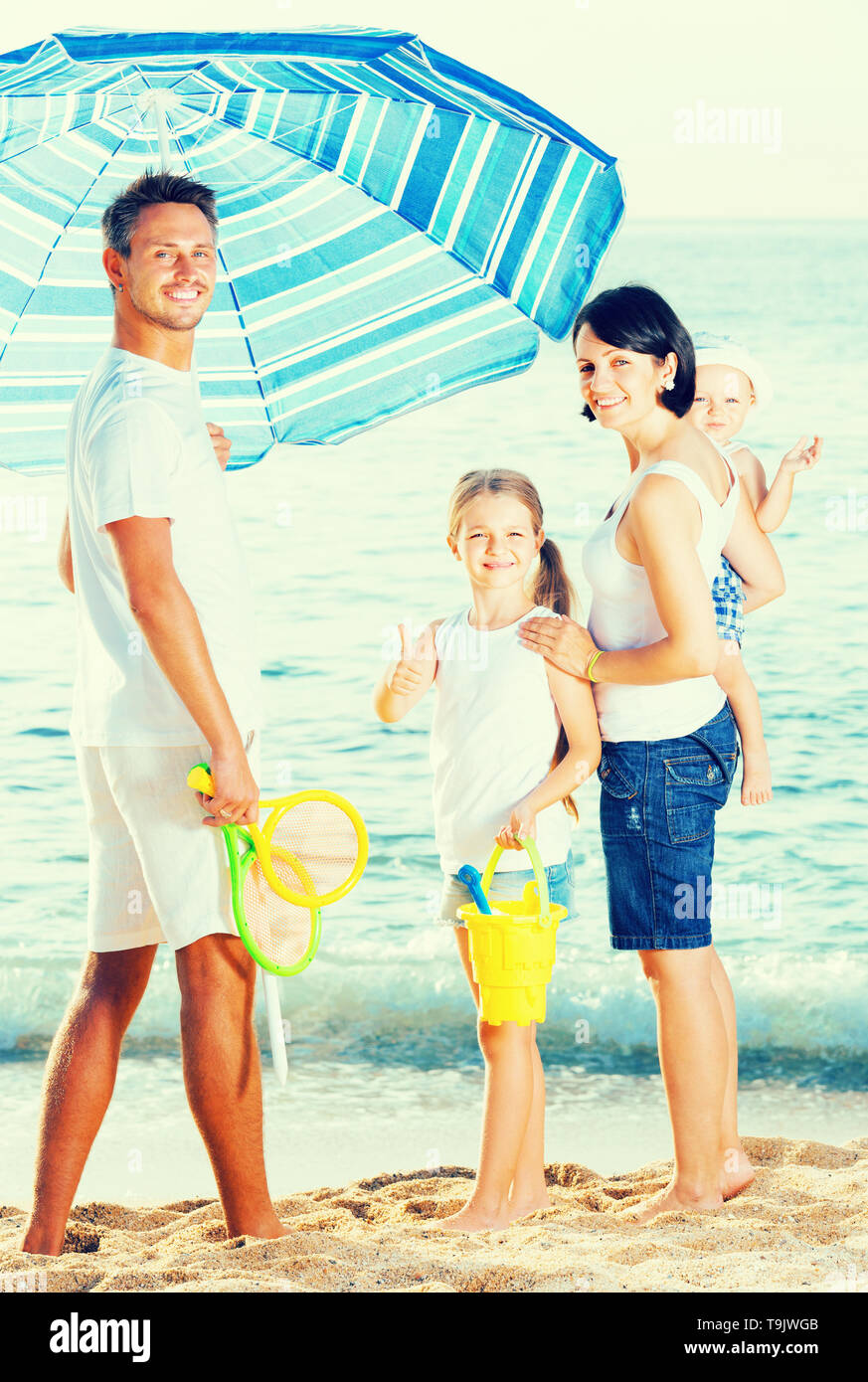 Happy spanish man and woman with two kids standing together under beach umbrella on beach - Stock Image