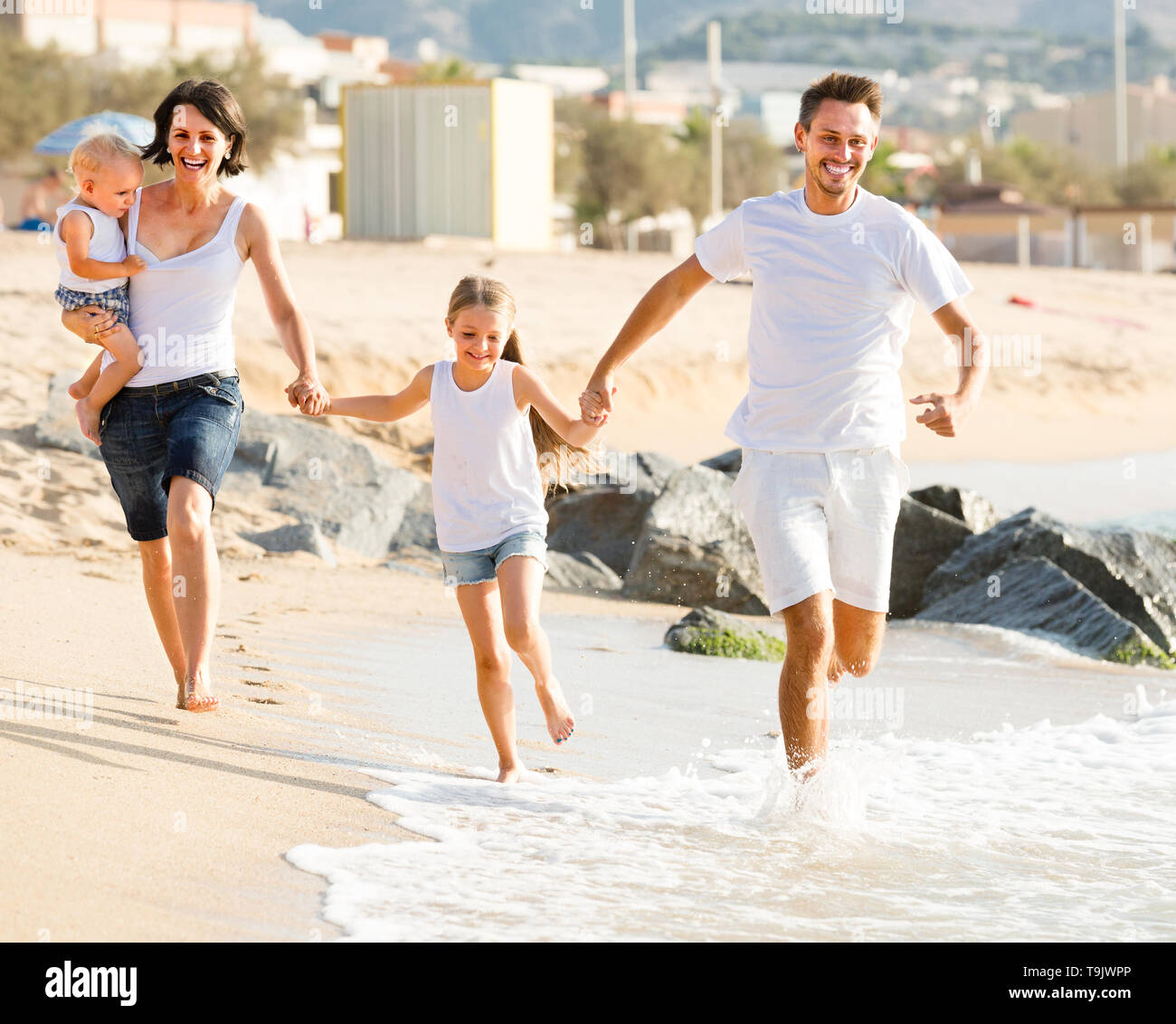 happy active couple with two children running on beach vacation - Stock Image