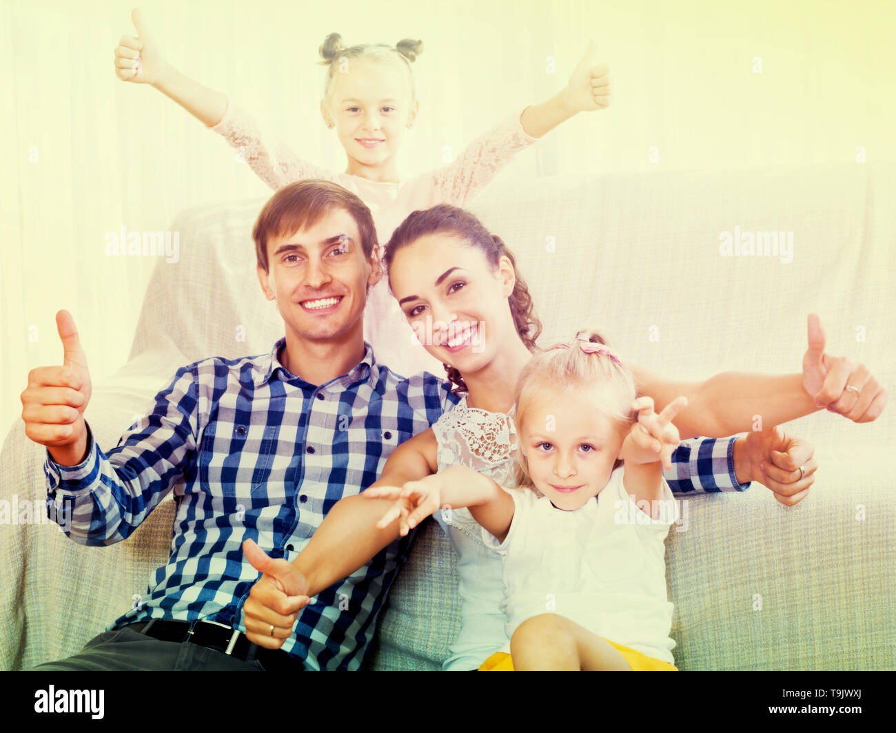 Relaxed smiling family of four persons posing in domestic interior - Stock Image