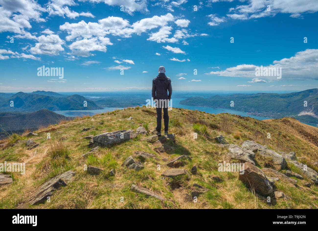 Lonely man, lone male hiker looks at Lake Maggiore from the summit of a nearby mountain. Summit view, solitude on the top, hiker on the trail. Stock Photo