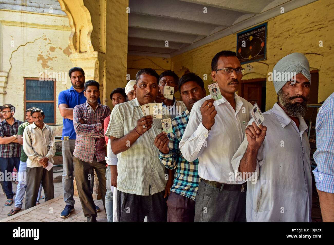 Indian voters seen showing their identity cards as they queue to cast their vote at a polling station during the final phase of India's general election in Patiala district of Punjab. Voting has begun for the final phase of Lok Sabha elections in Punjab, Bihar, West Bengal, Madhya Pradesh, Uttar Pradesh, Himachal Pradesh, Jharkhand and Chandigarh. Over 10.01 lakh voters will decide the fate of 918 candidates. The counting of votes will take place on May 23, officials said. - Stock Image