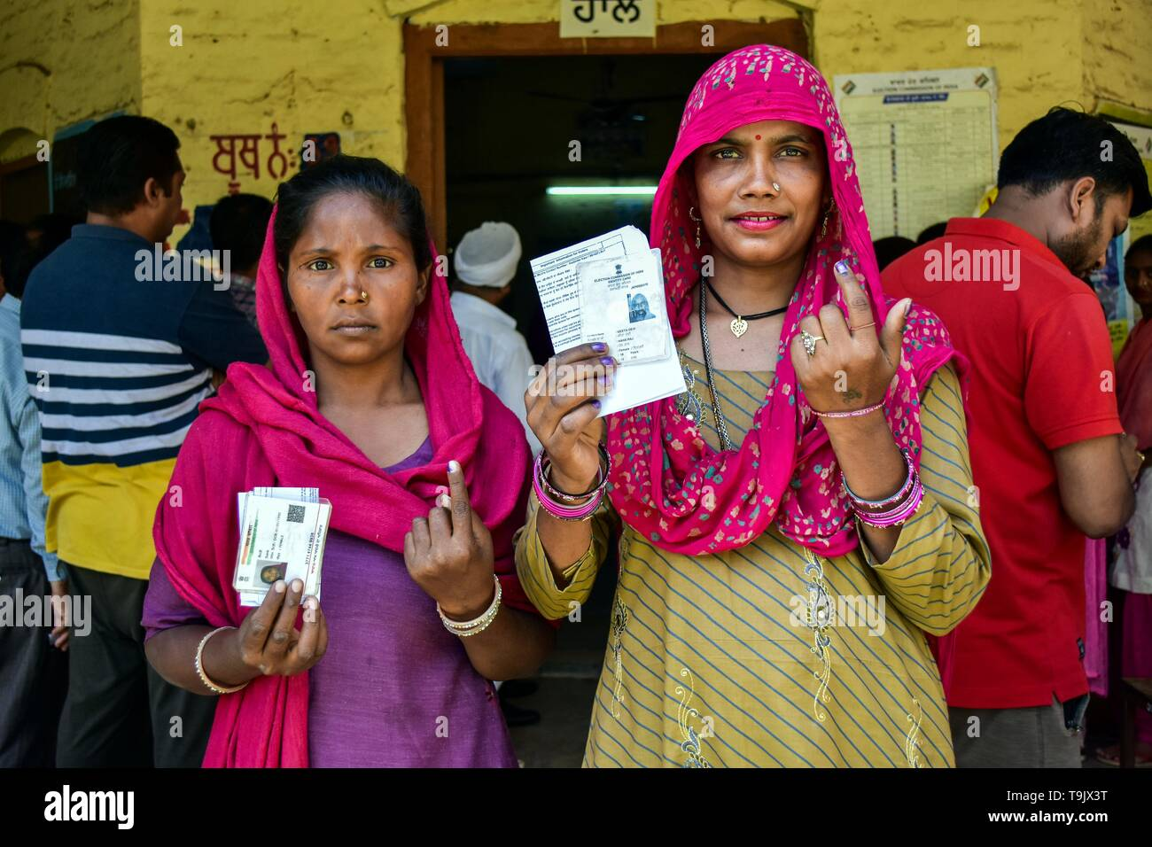 Indian voters seen showing their identity card and ink finger after casting her vote at a polling station during the final phase of India's general election in Patiala district of Punjab. Voting has begun for the final phase of Lok Sabha elections in Punjab, Bihar, West Bengal, Madhya Pradesh, Uttar Pradesh, Himachal Pradesh, Jharkhand and Chandigarh. Over 10.01 lakh voters will decide the fate of 918 candidates. The counting of votes will take place on May 23, officials said. - Stock Image