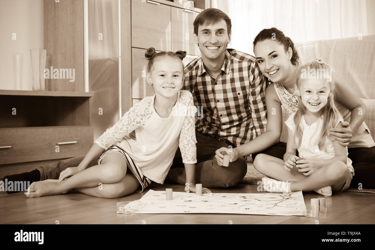 Smiling young family of four playing at board game in domestic interior - Stock Image