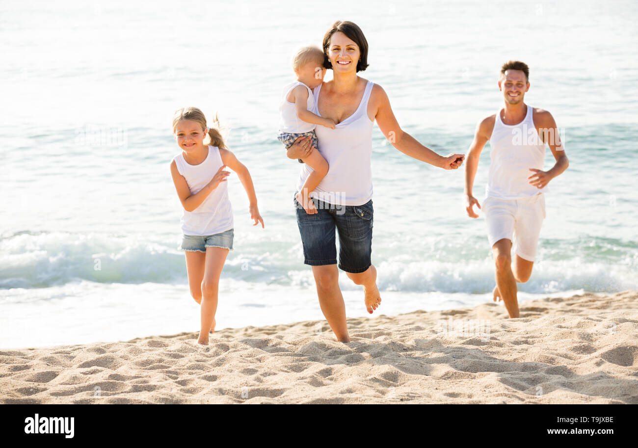 american couple with two children running on beach vacation - Stock Image