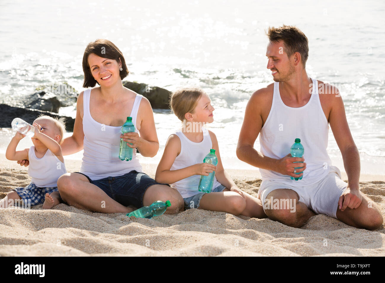 smiling young parents with two kids sitting together on sandy beach and drinking fresh water - Stock Image