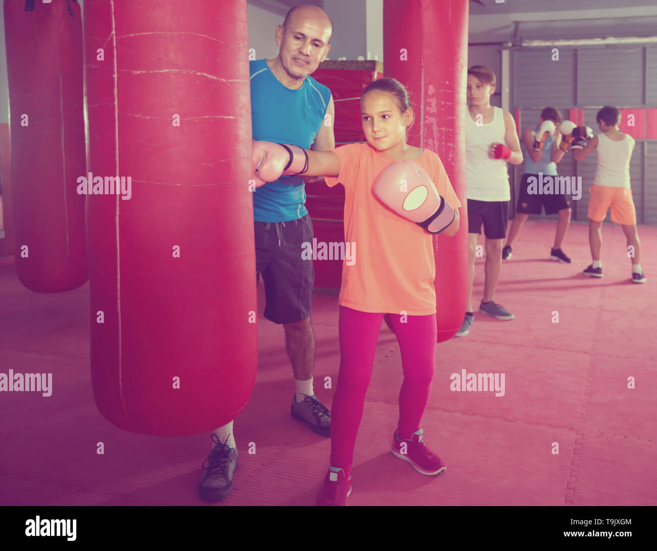 Girl teenager at boxing workout on punching bag with instructor - Stock Image