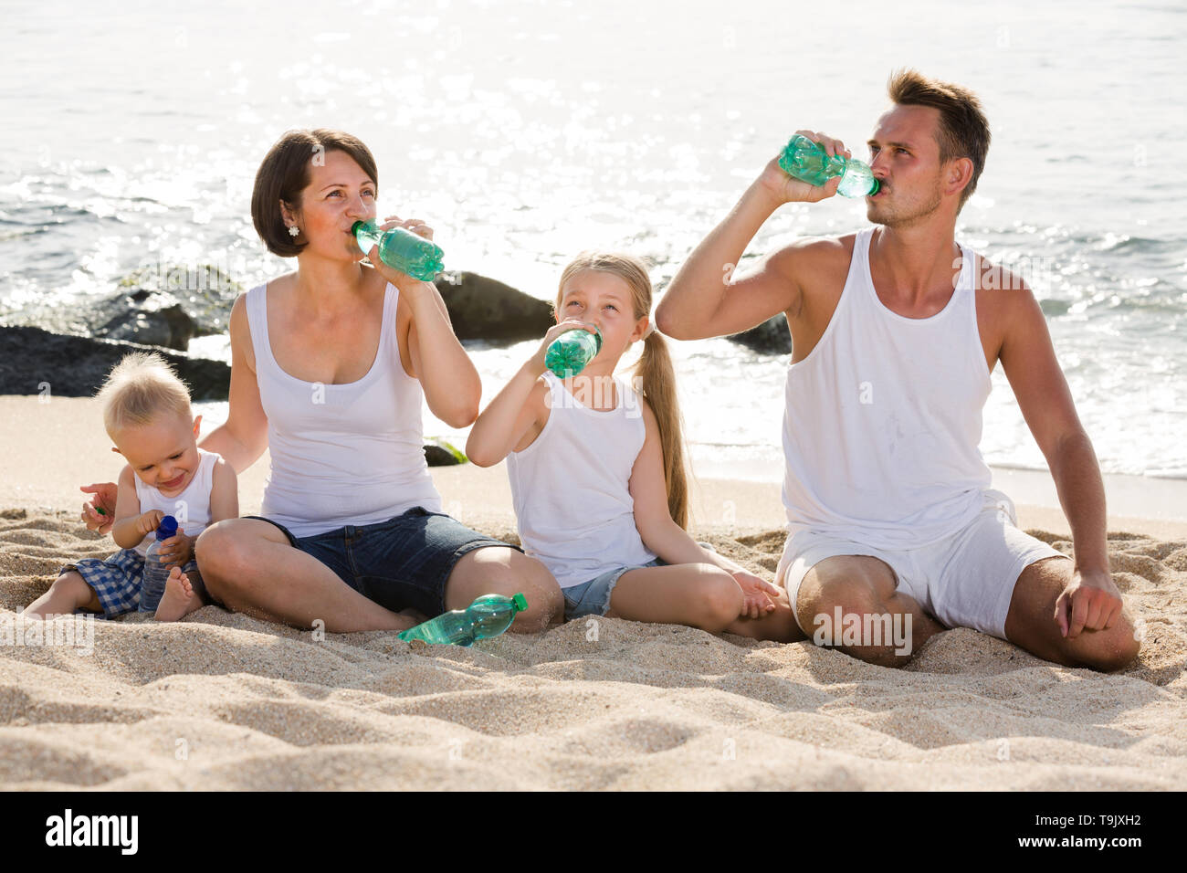 happy young parents with two kids sitting together on sandy beach and drinking fresh water - Stock Image