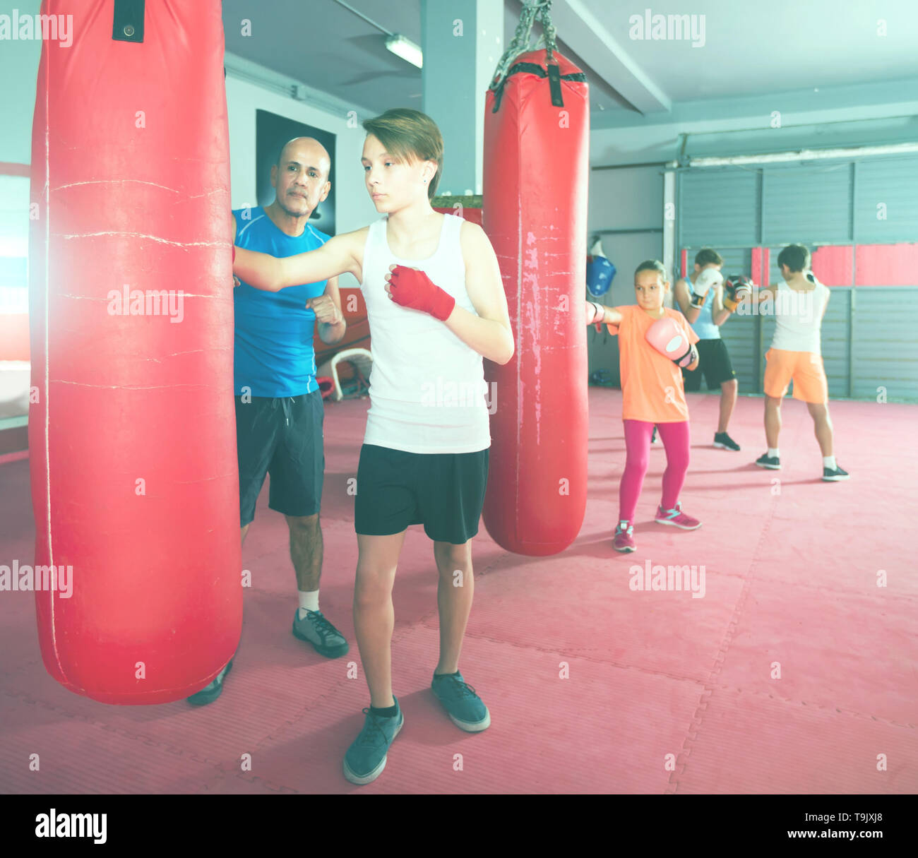 Young boxer earns blows on the punching bag under the supervision of the coach - Stock Image