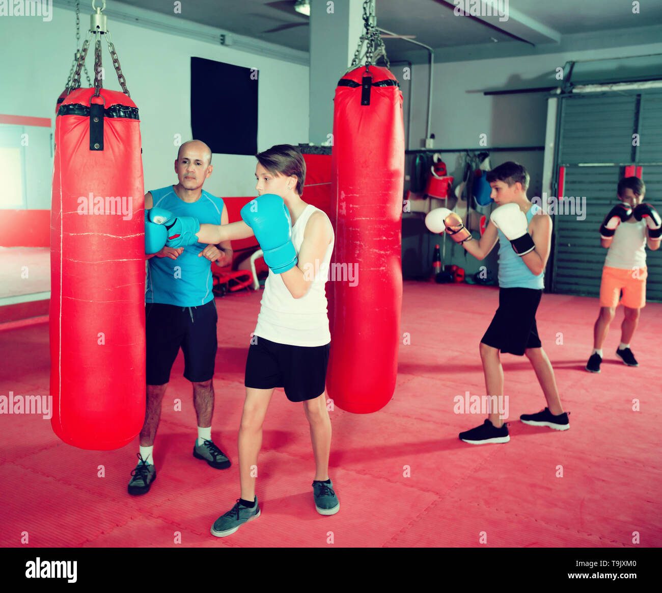 Boxing instructor and glad young children practicing blows on boxing bag - Stock Image