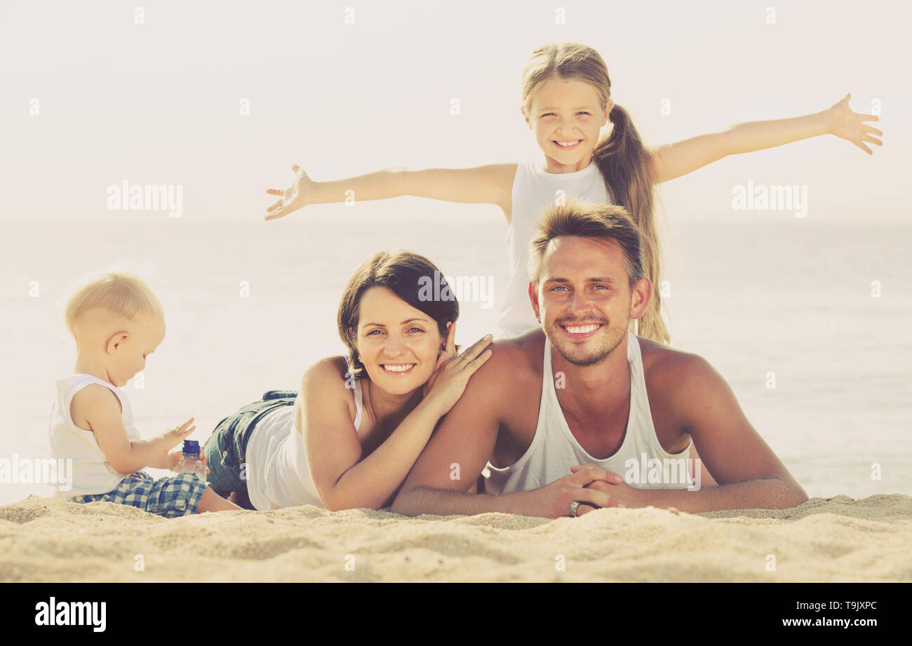 happy smiling young parents with two kids lying together on sandy beach on sunny day - Stock Image