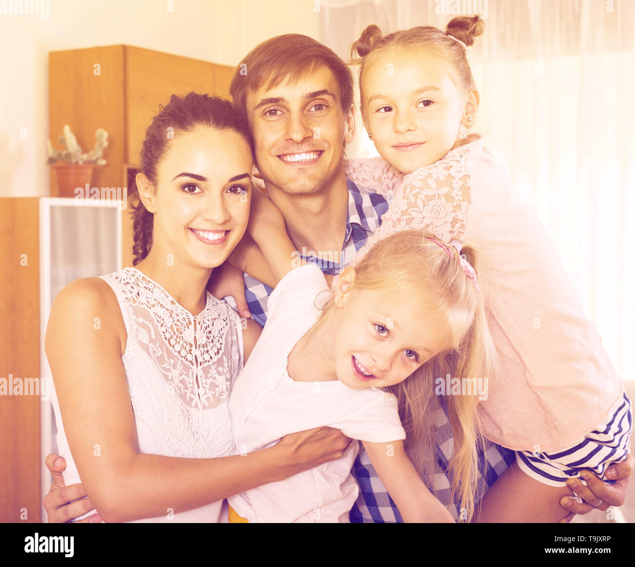 Family values: portrait of russian parents with little girls indoors - Stock Image