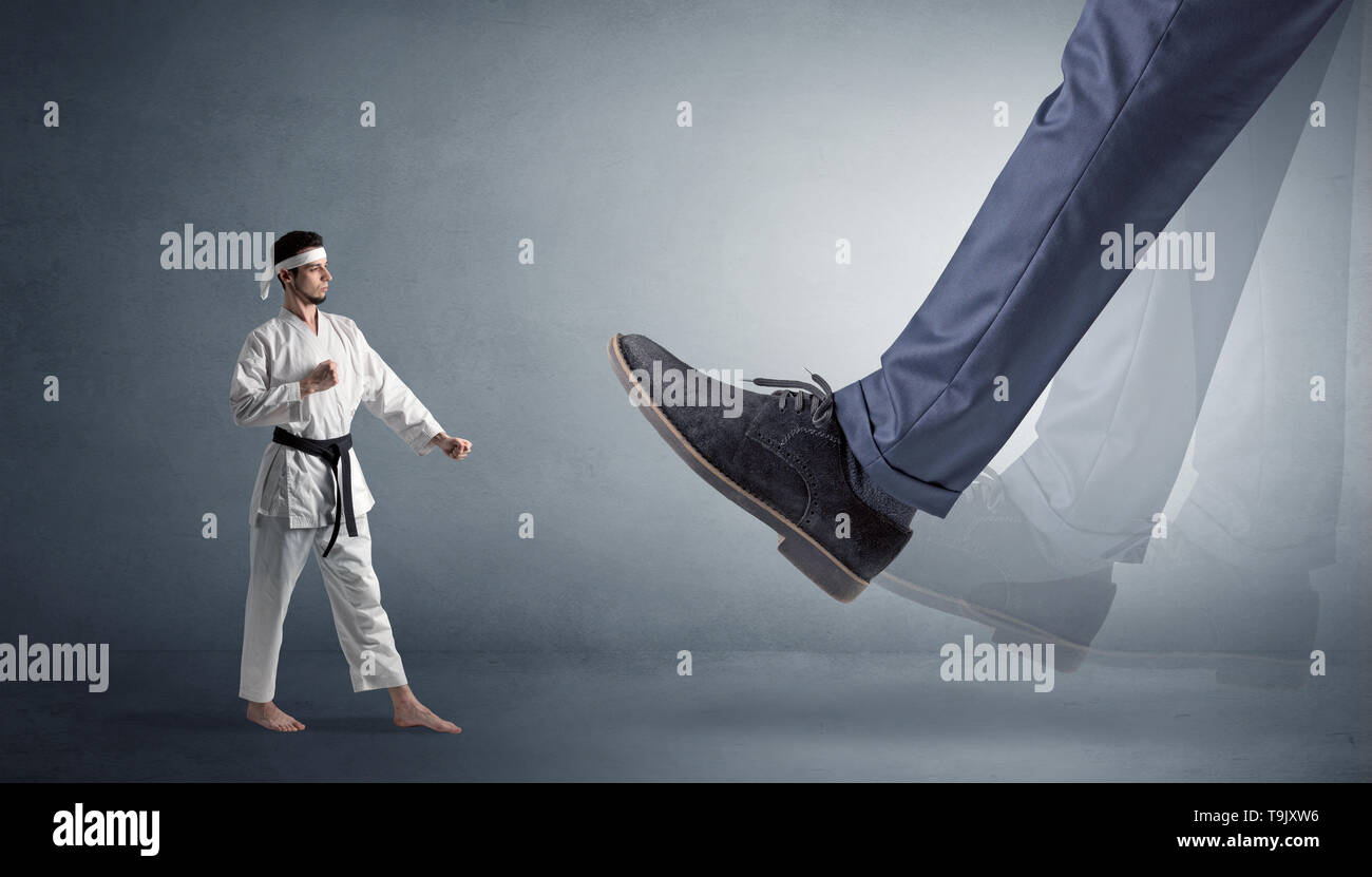Big foot treading small young karate man - Stock Image