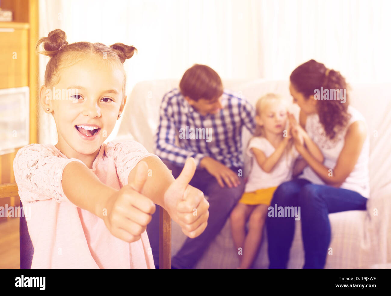 Family values: portrait of american parents with little girls indoors. focus on girl - Stock Image