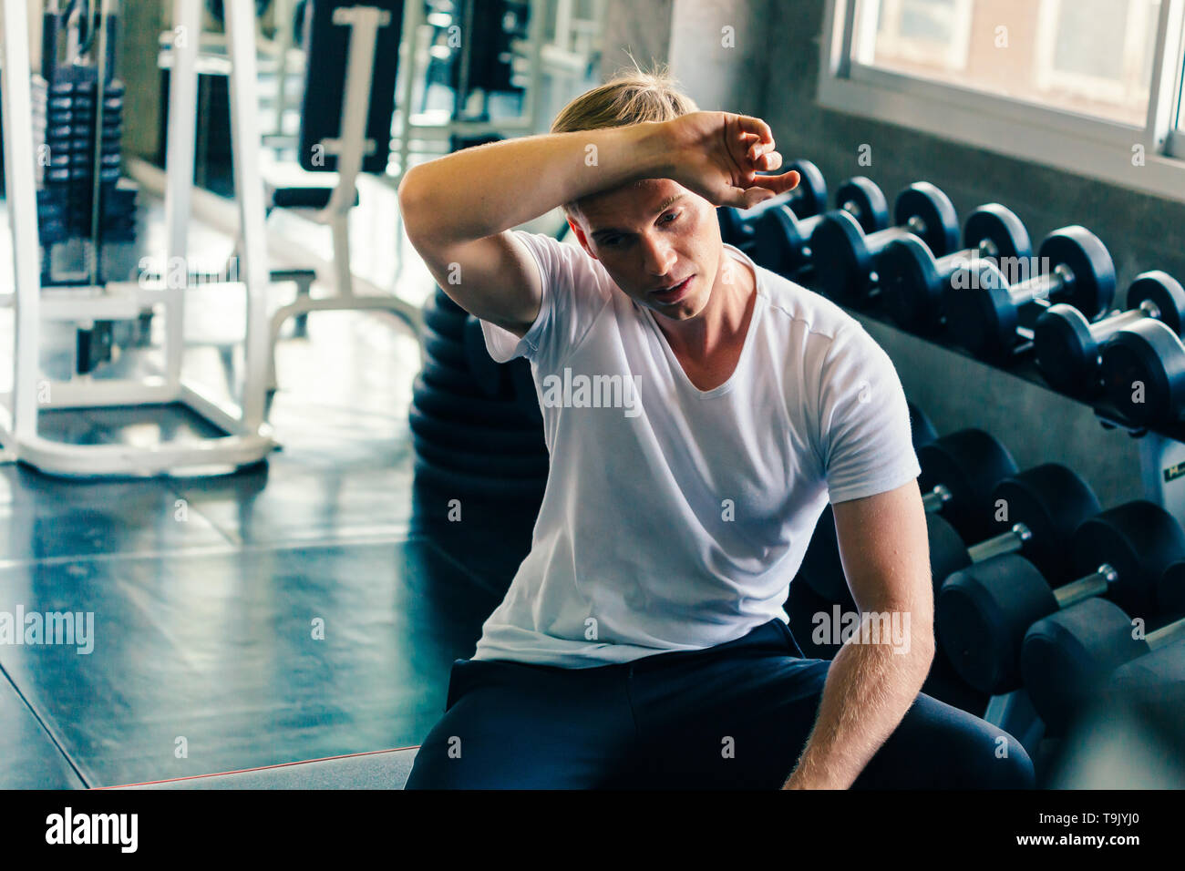 Young man wiping sweat off forehead with dumbbells and fitness equipment inside gym. He is tired and exhausted from weightlifting and weight training. - Stock Image